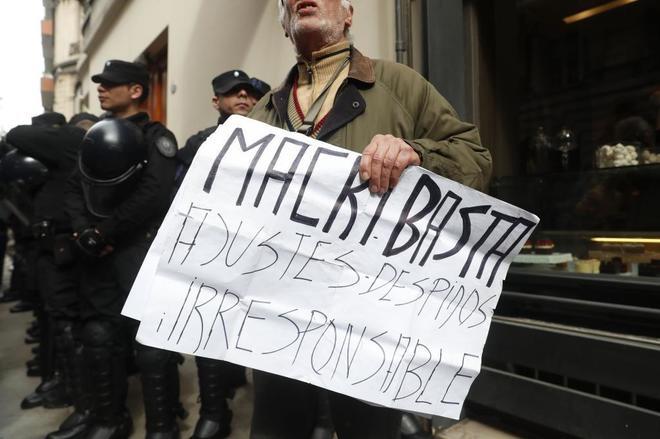 Un hombre sostiene un cartel mientras la Policía allana la casa de Kirchner.