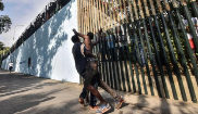 Dos de los hombres que lograron cruzar la valla saludan a quienes les...