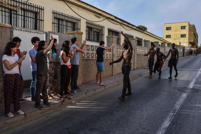 Varias personas reciben con aplausos a los inmigrantes que llegan a...