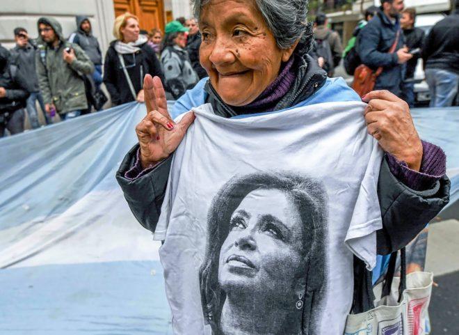 Una seguidora de Cristina Kirchner se manifiesta mientras la policía registra la casa de la ex mandataria.