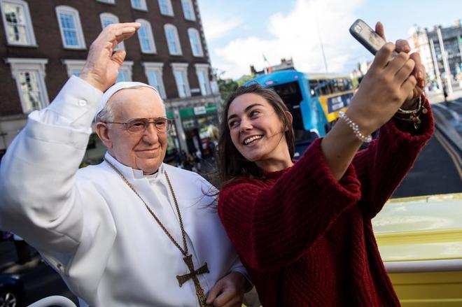 Una joven se fotografía junto a una estatua de cera del papa Francisco en Dublín, Irlanda.