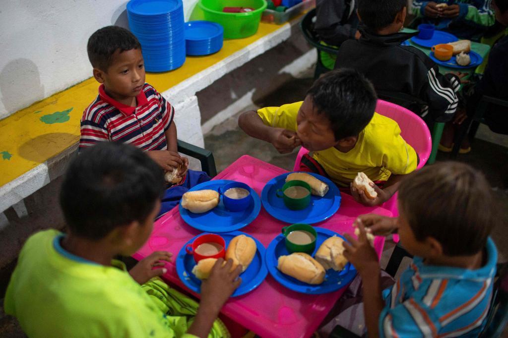 Niños venezolanos desayunan en el 'Café Fraterno' del padre Jesús, en Pacaraima.