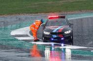 Un comisario habla con el coche de seguridad, este domingo en Silverstone.