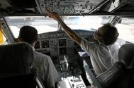 Pilotos en la cabina de un avión, listos para iniciar un vuelo.