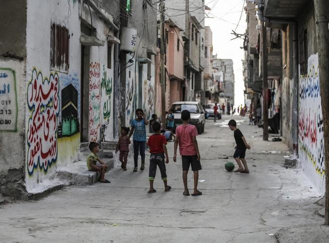 Niños palestinos juegan con una pelota en el campo de refugiados de...