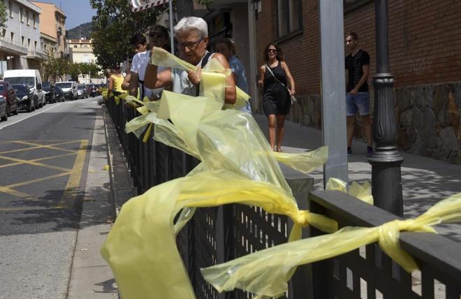 Un grupo de personas coloca plásticos amarillos a modo de lazos en...