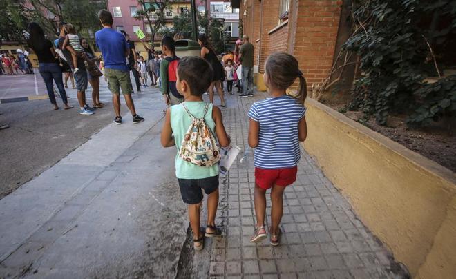 Dos niños acuden al colegio en el primer día del curso escolar...