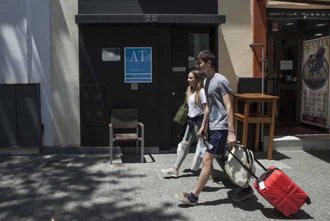 Unos turistas caminan por una calle del centro de Sevilla con sus maletas.