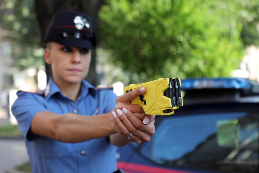 Una policía italiana muestra una pistola paralizante Taser.
