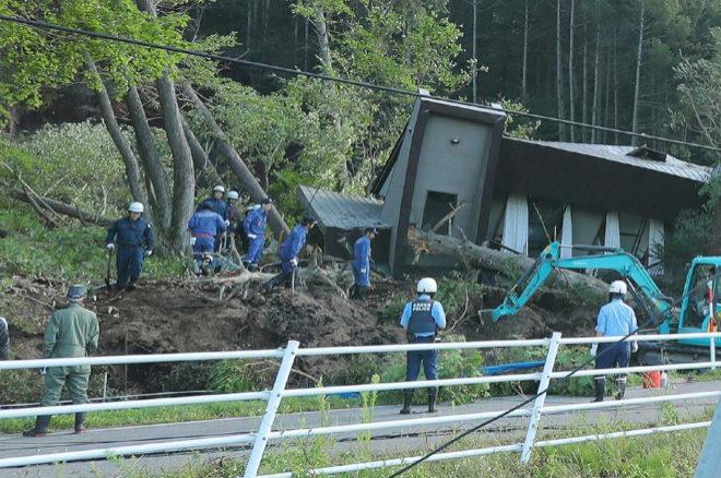 Policías y bomberos buscan supervivientes entre los restos de una casa en la ciudad de Atsuma (Japón).