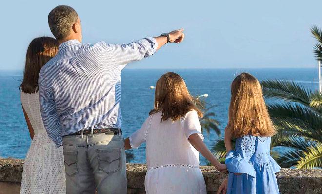 Los Reyes, con sus hijas, todos mirando el mar, en su tradicional posado en Palma de Mallorca, donde van todos los veranos.