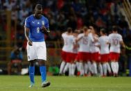 Balotelli se lamenta mientras los jugadores polacos celebran un gol.
