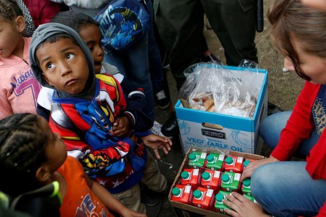 Niños venezolanos esperan para recibir comida en un campamento improvisado, en Bogotá.