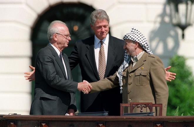 El presidente de EEUU Bill Clinton, entre el líder palestino Yasir Arafat y el primer ministro israelí Isaac Rabin, tras firmar los Acuerdos de Oslo, en Washington.