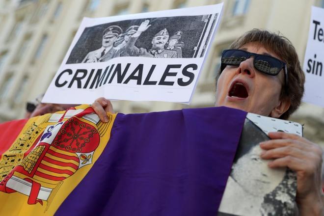 Una mujer participa en la protesta organizada hoy por víctimas del franquismo ante el Congreso.