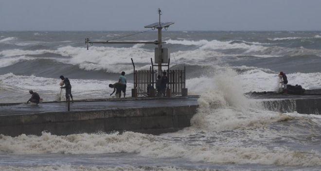 Hombres pescan en la orilla antes de la llegada del tifón, en Aparri, provincia de Cagayan.