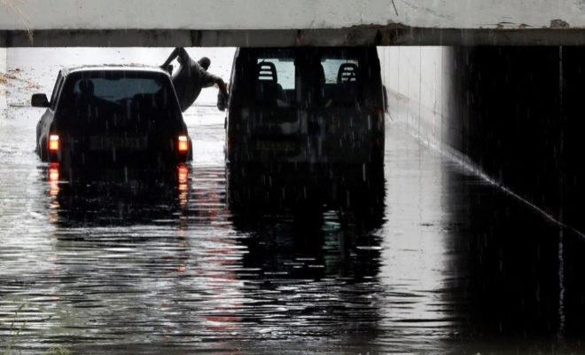 Una persona intenta salir de una furgoneta atrapada en un túnel de Alfafar debido a las intensa lluvias.