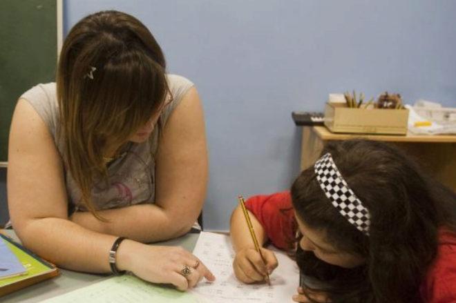 Una voluntaria ayuda a una niña a hacer los deberes dentro de un...