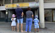 Luis y Rosa posan de espaldas con sus hijos a las puertas de la sede de la Seguridad Social.
