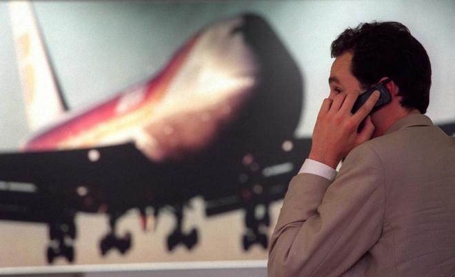 Un viajero habla con su móvil en un aeropuerto.