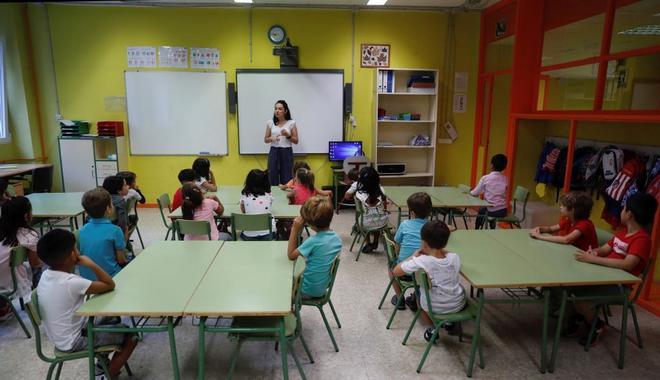 Los alumnos de un colegio de Madrid atienden a su profesora en el...