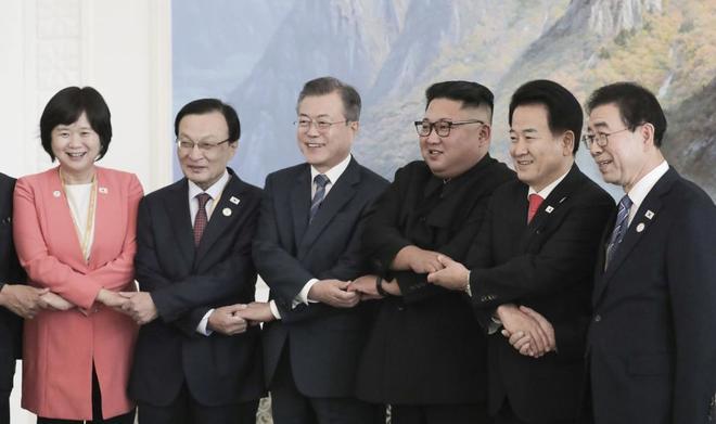 Sur Moon Jae-in y Kim Jong Un, celebrando el acuerdo con las delegaciones.