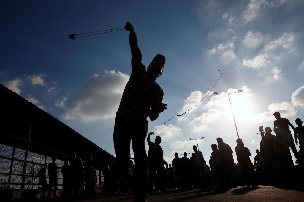 Un palestino lanza una piedra durante las protestas en la franja de Gaza.