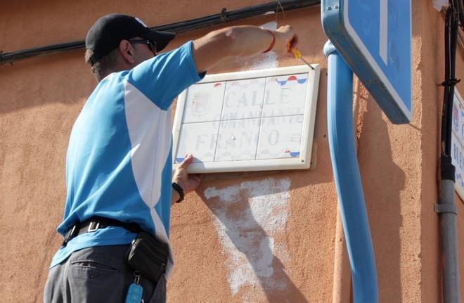 Un técnico desatornilla la placa dedicada al Comandante Franco en Alicante.