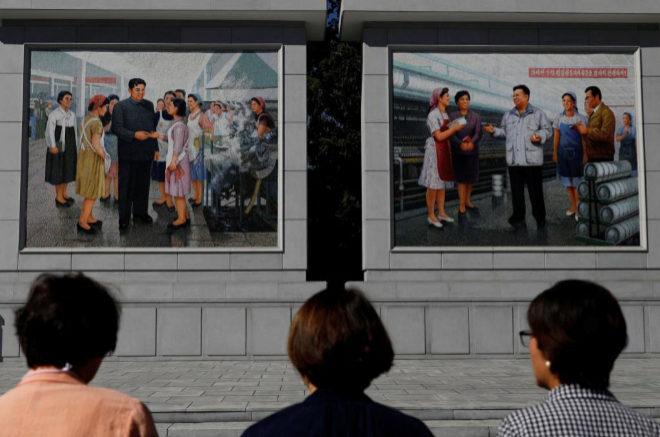 Tres mujeres coreanas observar los dibujos de antiguos líderes del país en una fábrica de Pyongyang.