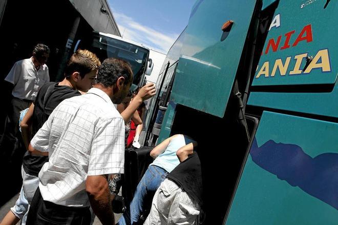 Un grupo de pasajeros carga su equipaje en un autocar.
