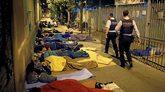Dos agentes de los Mossos caminan ante personas que duermen a la...