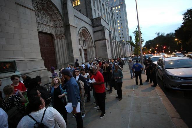 Varias personas hacen fila en la puerta de la iglesia Riverside de Harlem.