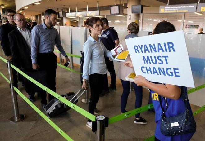 Pasajeros, en su embarque en vuelos de Ryanair este viernes en España, ante un cartel de protesta.