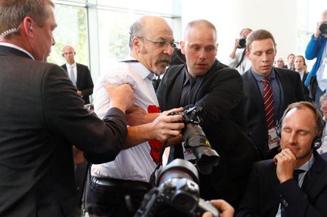 Un periodista es expulsado por los guardias de seguridad de la rueda de prensa.