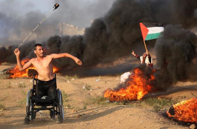 Un manifestante en silla de ruedas lanza una piedra contra fuerzas israelíes durante una protesta en Gaza.