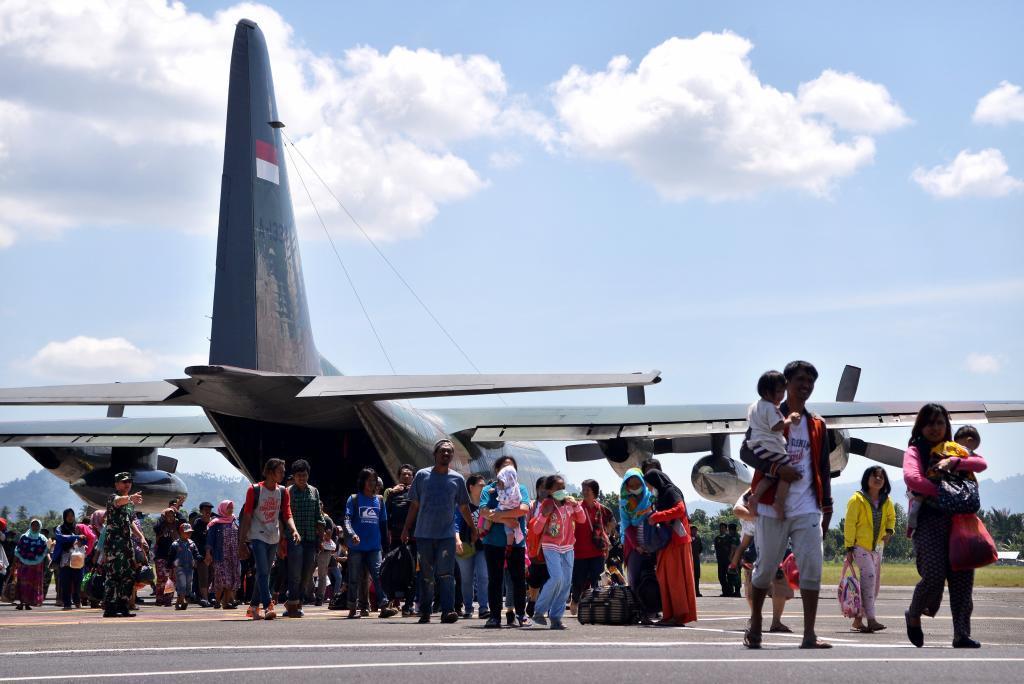 Decenas de personas esperan en el aeropuerto de Manado, Indonesia, para ser evacuadas tras el tsunami.