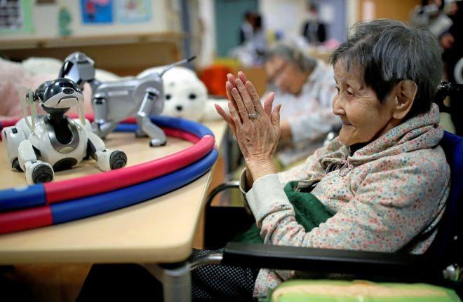 Una anciana aplaude a su perro robot en una residencia en Tokyo (Japón)