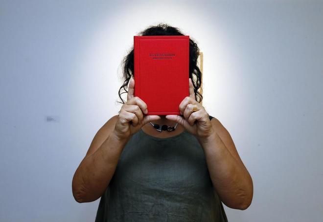Begoña Deltell sostiene un ejemplar de 'La vida dañada', el libro que ha editado con la obra de Sinaga a quien ha entrevistado Peio Aguirre.