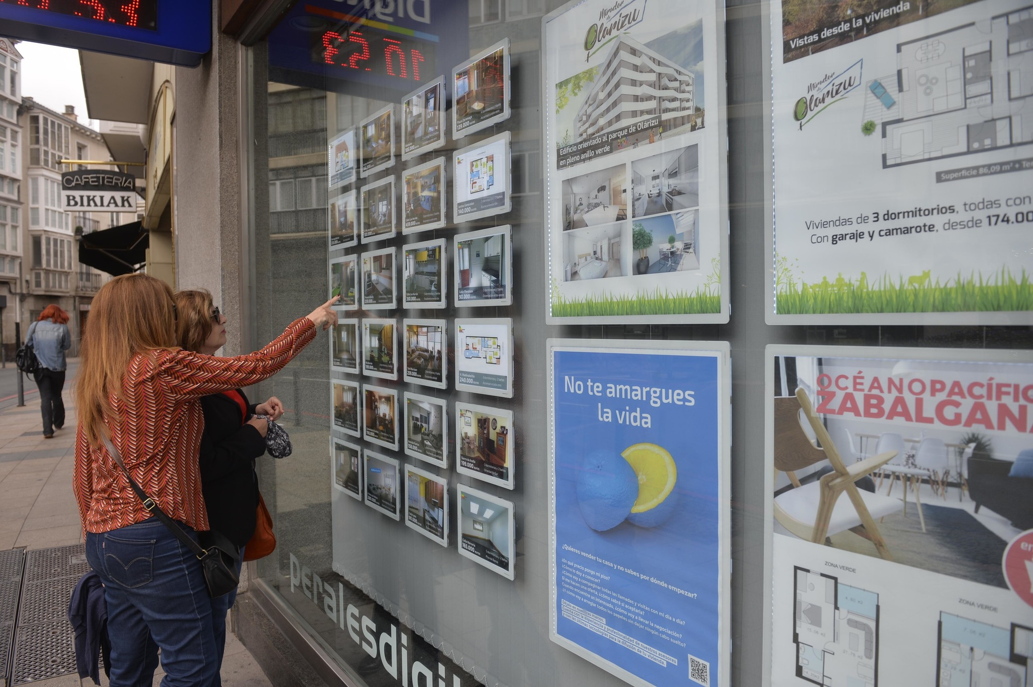 Unas mujeres miran los anuncios de vivienda en venta en una inmobiliaria.