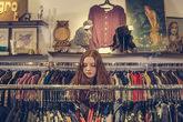 Una chica rebusca entre los percheros de una tienda de moda.