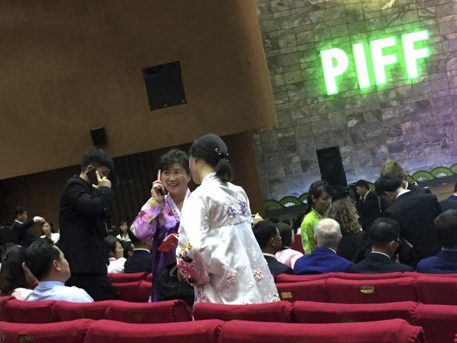 Varias personas del público esperan a uno de los pases en la Casa Internacional del Cine de Pyongyang.