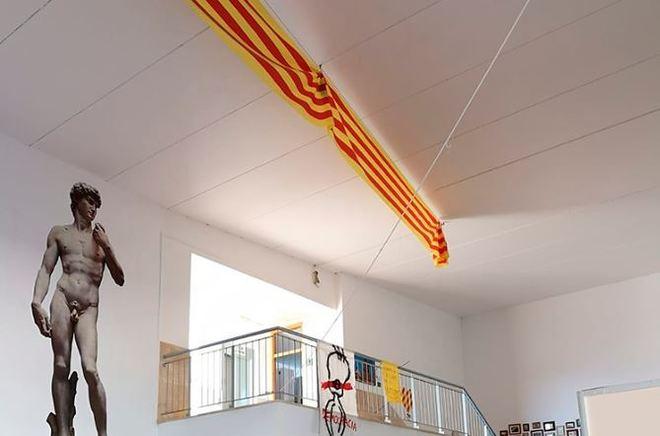 Colgados de la escalera se muestran dos carteles en clara alusión al conflicto catalán.