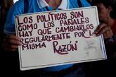 Un hombre con una pancarta reivindicativa participa en una protesta...