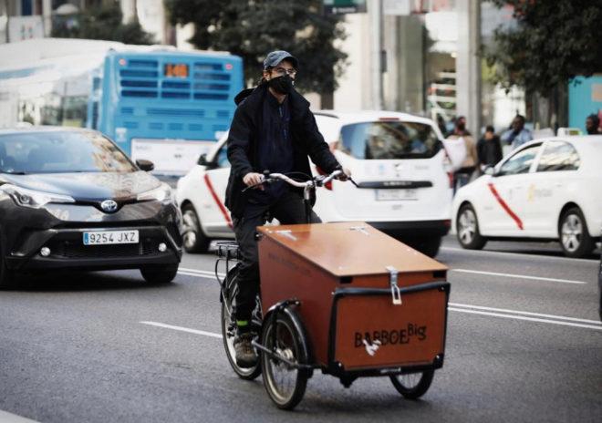Un ciclista con una máscara entre el tráfico de Madrid