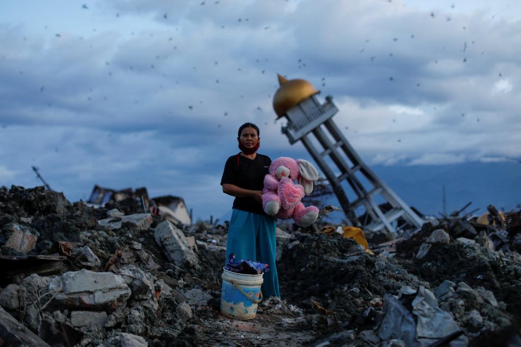 Una mujer sujeta un peluche encontrado entre los escombros de lo que fue su hogar en Palu.
