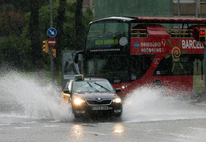Un taxi y un autobús turístico afectados por la lluvia caída esta...
