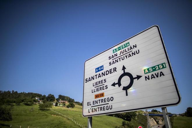 Un cartel indica direcciones en una carretera asturiana con la toponimia en bable y castellano.