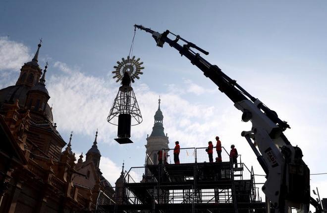 Operarios municipales colocan la imagen de la Virgen del Pilar para la...