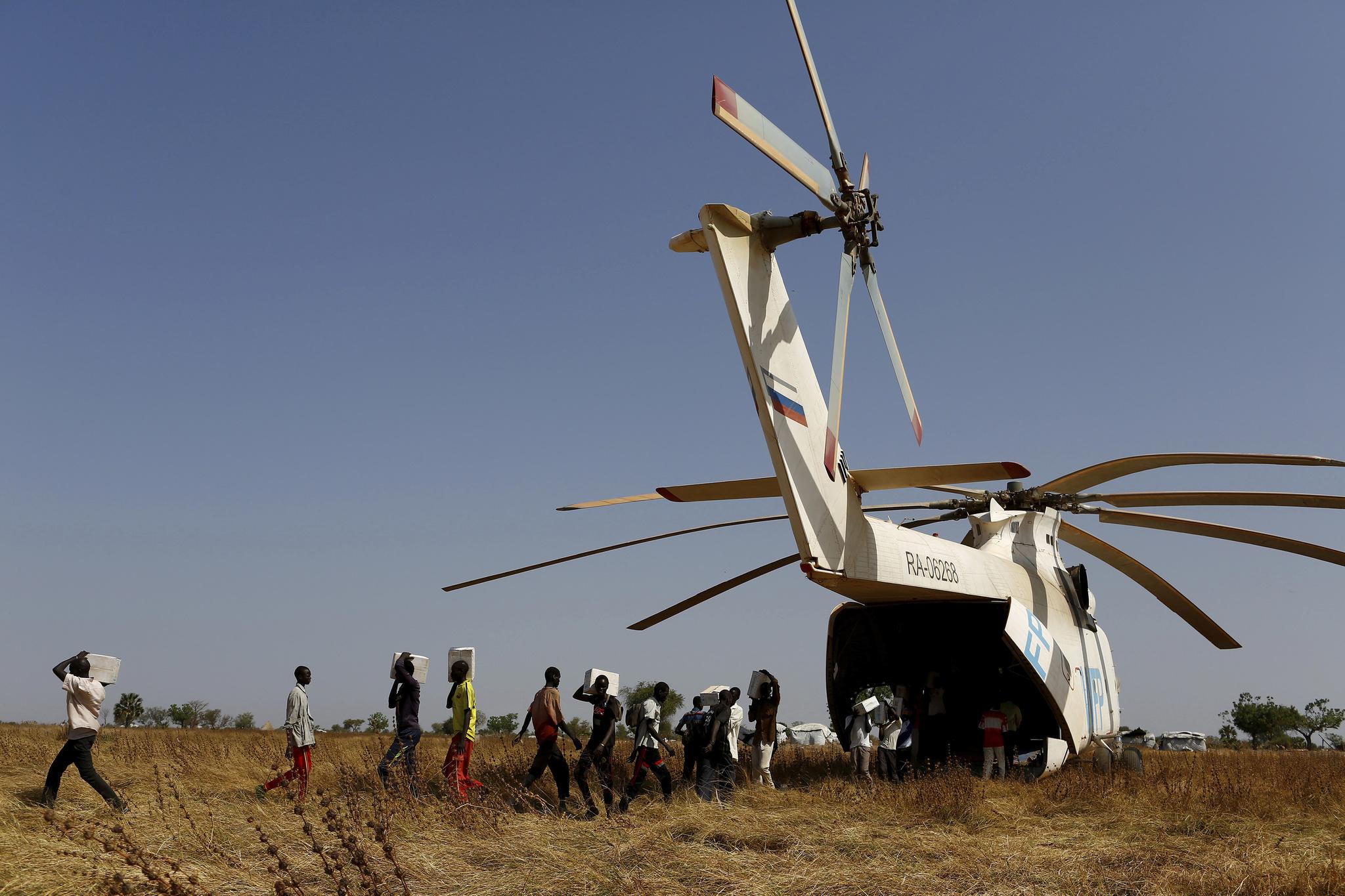 Una fila de hombres descarga ayuda humanitaria de un helicóptero en Thonyor (Sudán del Sur).