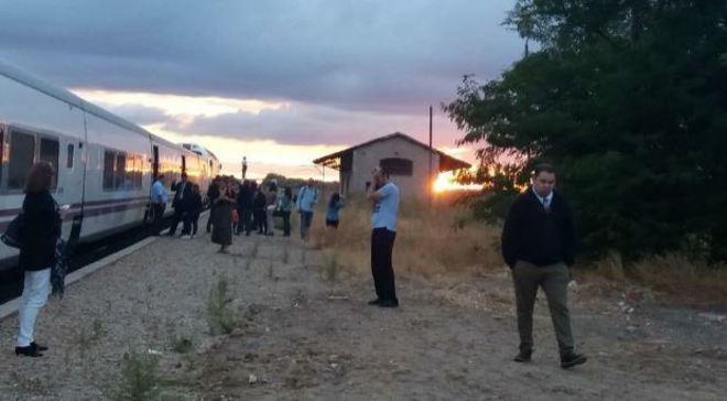 Pasajeros esperan la reparación de un tren que quedó detenido en el campo.